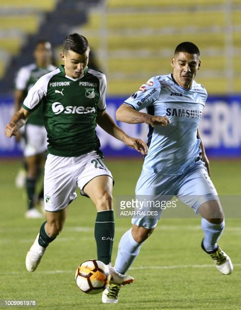 Player Pablo Pedraza of Bolivian Bolivar vies for the ball with Nicolas Benedetti of Deportivo Cali of Colombia during a Copa Sudamericana football...