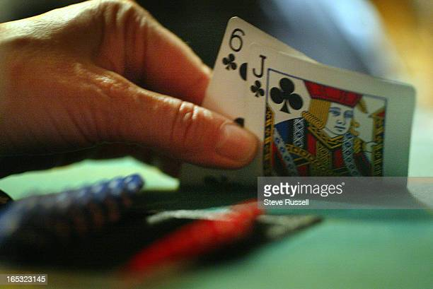 HOLD 'EM POKER03/07/05A player peeks at their hand the popularity of Texas Hold 'Em Poker is increasing both online and in person Philthy McNasty's...
