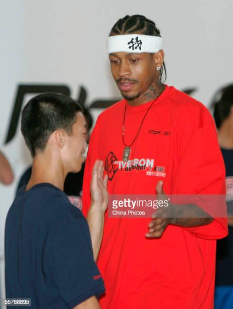 NBA player Philadelphia 76ers guard Allen Iverson cheers with a young boy as he plays basketball with orphans at Shanghai Children's Welfare Center...
