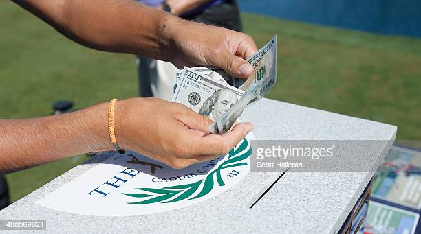 A player puts cash into the caddie competition cash box on the 17th tee during a practice round ahead of THE PLAYERS Championship on The Stadium...