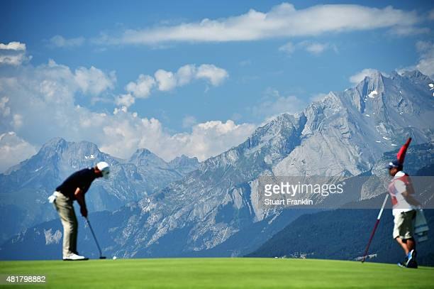 A player putts with the Alps in the background during the second round of the Omega European Masters at CranssurSierre Golf Club on July 24 2015 in...