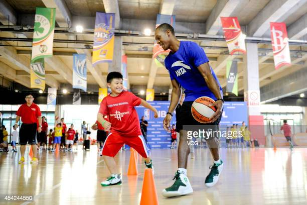 NBA player Rajon Rondo of the Boston Celtics plays basketball with children at the NBA Yao School on August 27 2014 in Beijing China