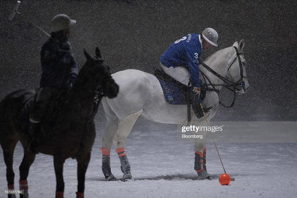 A player reaches for the ball at the annual Klosters Snow Polo event in Klosters, Switzerland, on Friday, Jan. 20, 2012. German Chancellor Angela Merkel will open next week's World Economic Forum in Davos, Switzerland, which will be attended by policy makers and business leaders including U.S. Treasury Secretary Timothy F. Geithner. Photographer: Scott Eells/Bloomberg via Getty Images