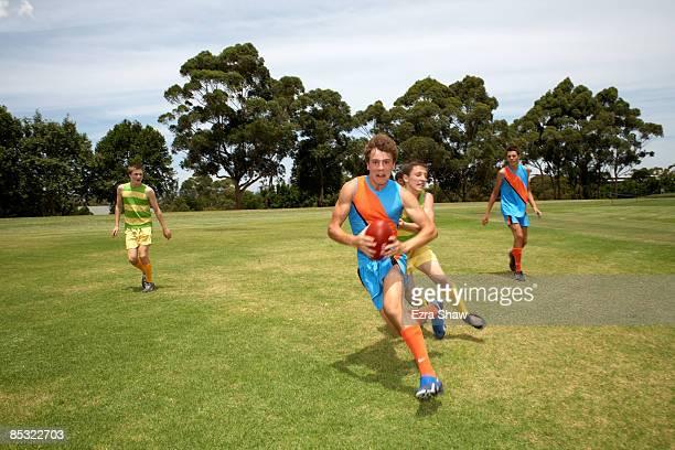 player running from opposition with football - australian rules football stock-fotos und bilder
