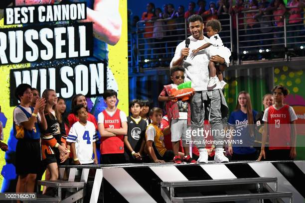 NFL player Russell Wilson accepts the Best Cannon award with Future Zahir Wilburn and Sienna Princess Wilson onstage during the Nickelodeon Kids'...
