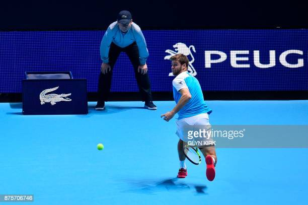 US player Ryan Harrison returns through his legs as he plays with his partner New Zealand's Michael Venus against Brazil's Marcelo Melo and Poland's...