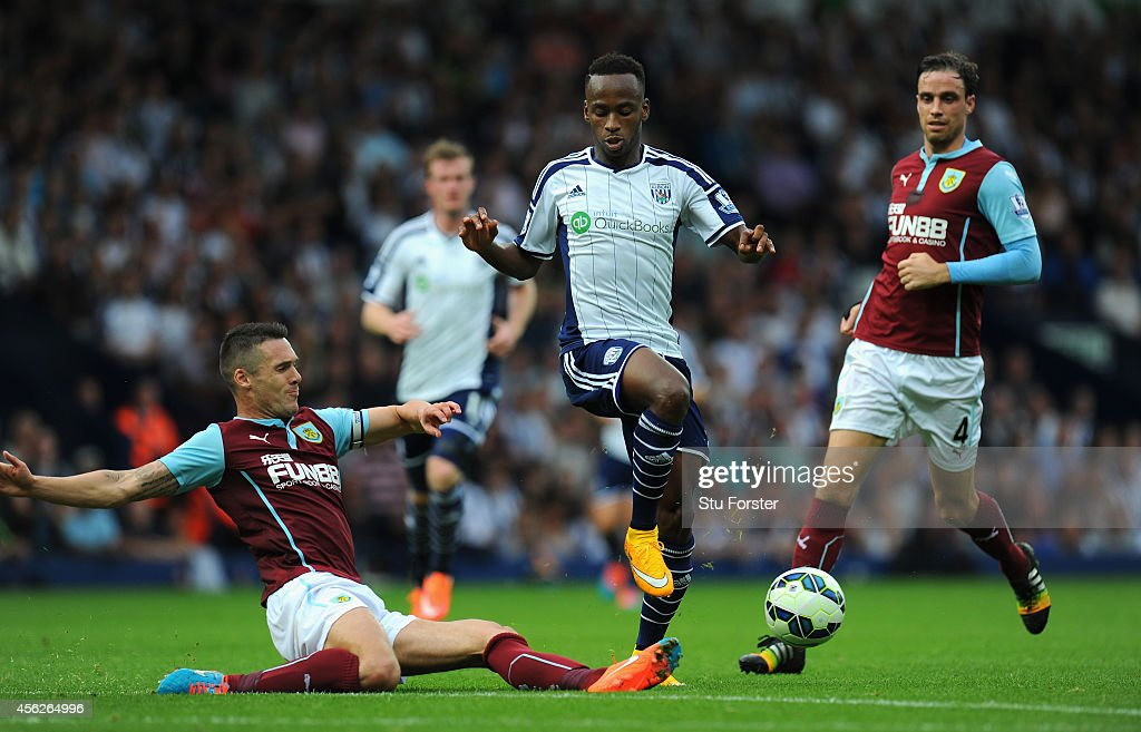 WBA player Saido Berahino (c) skips the challenge of Jason Shackell (l) during the Barclays Premier League match between West Bromwich Albion and Burnley at The Hawthorns on September 28, 2014 in West Bromwich, England.
