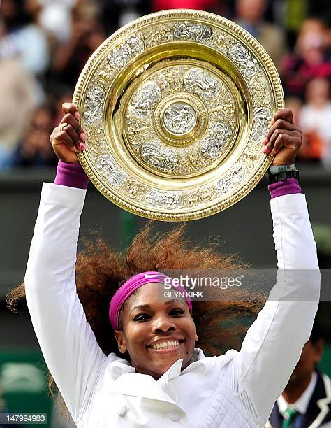 US player Serena Williams celebrates with the trophy the Venus Rosewater Dish after her women's singles final victory over Poland's Agnieszka...