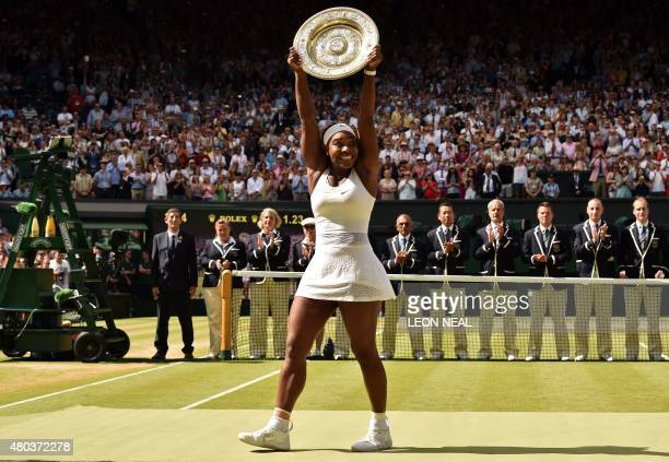 Player Serena Williams celebrates with the winner's trophy, the Venus Rosewater Dish, after her women's singles final victory over Spain's Garbine...