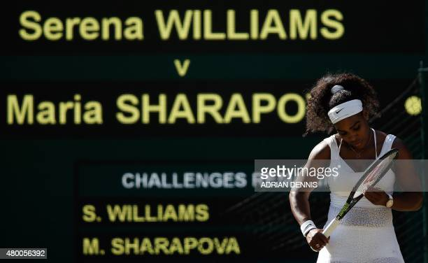 US player Serena Williams checks her racquet between points against Russia's Maria Sharapova in their women's semifinal match on day ten of the 2015...