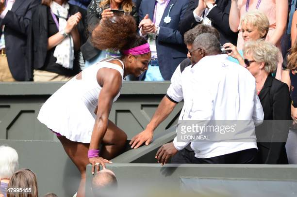 US player Serena Williams climbs into the Royal Box to celebrate with her father Richard after her women's singles final victory over Poland's...