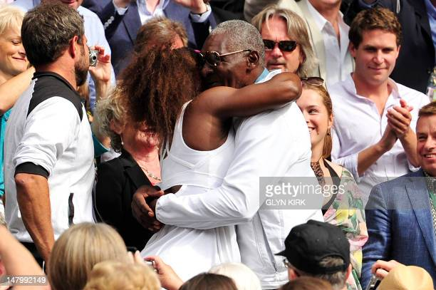 US player Serena Williams climbs up into the Royal Box to embrace her father Richard WIlliams after her women's singles final victory over Poland's...