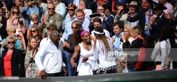 US player Serena Williams climbs up into the Royal Box to embrace her sister Venus WIlliams after her women's singles final victory over Poland's...