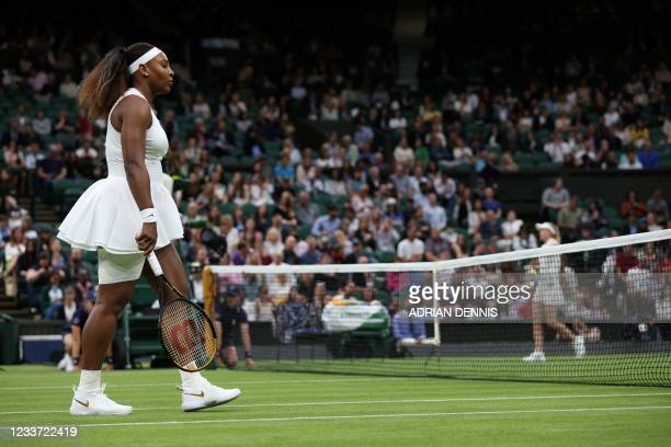 Player Serena Williams passes Belarus's Aliaksandra Sasnovich as they swap ends during their women's singles first round match on the second day of...