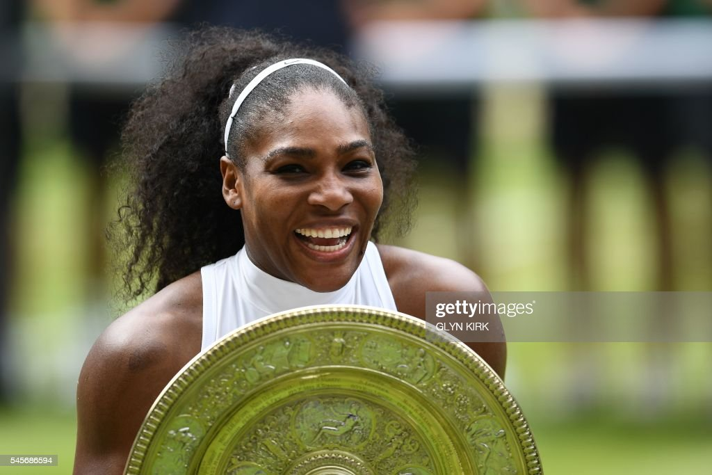 TOPSHOT - US player Serena Williams poses with the winner's trophy, the Venus Rosewater Dish, after her women's singles final victory over Germany's Angelique Kerber on the thirteenth day of the 2016 Wimbledon Championships at The All England Lawn Tennis Club in Wimbledon, southwest London, on July 9, 2016. /