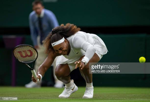 Player Serena Williams reacts as she pulls-up injured before withdrawing from her women's singles first round match against Belarus's Aliaksandra...