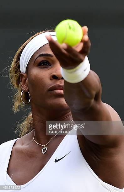 US player Serena Williams serves to France's Alize Cornet during their women's singles third round match on day six of the 2014 Wimbledon...