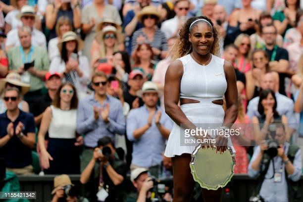 Player Serena Williams smiles as she poses with her trophy after being beaten by Romania's Simona Halep during their women's singles final on day...