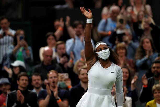 Player Serena Williams waves to the fans after withdrawing from her women's singles first round match against Belarus's Aliaksandra Sasnovich on the...