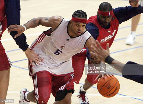 Player Shannon Brown of the Cleveland Cavaliers is chased by teammate Larry Hughes during a training session before their 17 October exhibition match...
