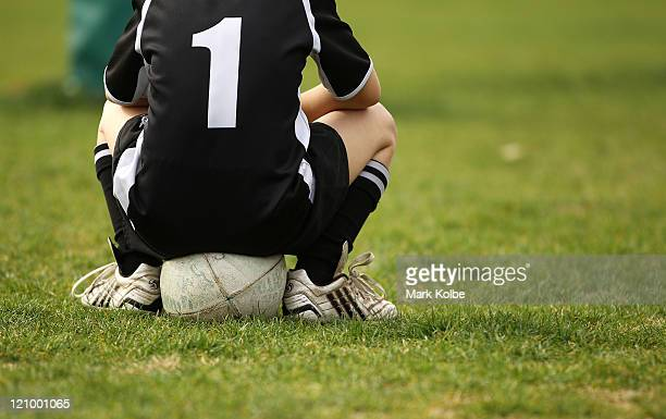 A player sits on a rugby ball as he watches on during the under 10's junior rugby union semi finals at Nagle Park on August 13 2011 in Sydney...