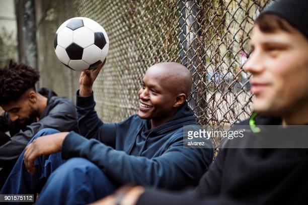 Player sitting with his soccer team against fence