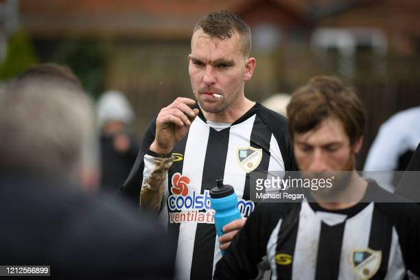 A player smokes a cigarette during the half time team talk during Sunday league football between Syston Brookside FC and Shepshed Oaks FC on March 15...