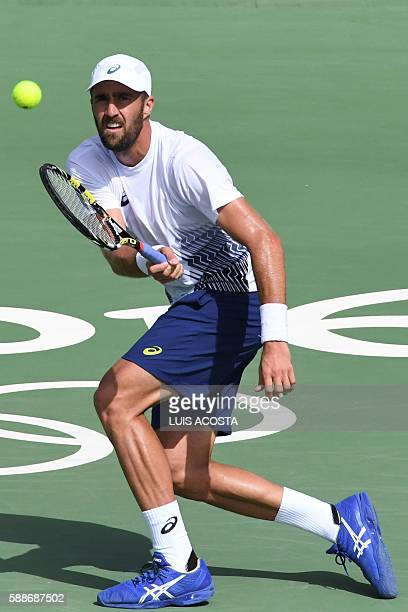 Player Steve Johnson returns the ball to Britain's Andy Murray during their men's singles quarter-finals tennis match at the Olympic Tennis Centre of...