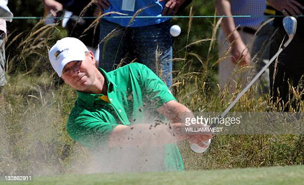 Player Steve Stricker chips out of a bunker during a practice round for the President's Cup golf event at the Royal Melbourne golf course, in...