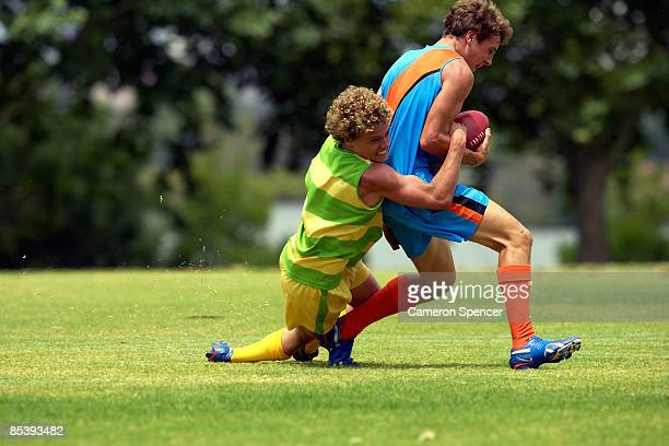 player tackles his opposition in football game - afl stock pictures, royalty-free photos & images
