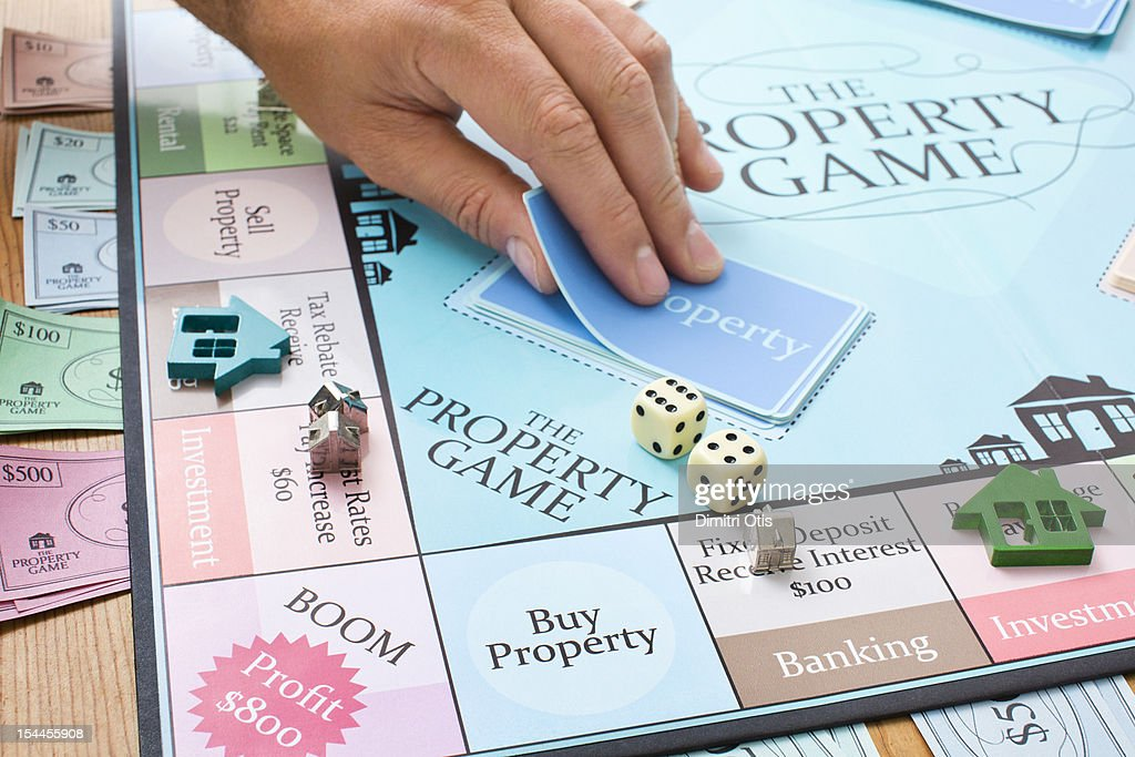 Player taking card from property board game : Stock Photo