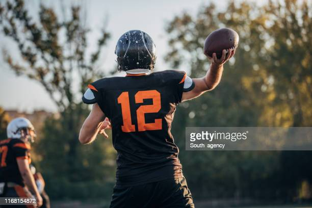 nfl player throwing a ball - passing sport imagens e fotografias de stock
