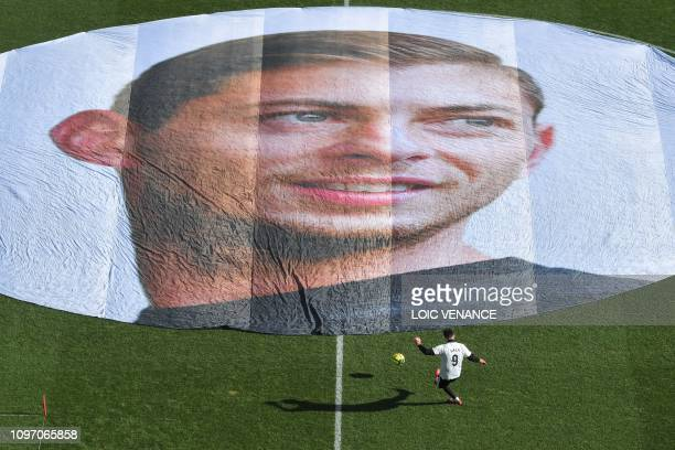 TOPSHOT A player trains in front of the portrait of Argentinian forward Emiliano Sala prior to the L1 football match between FC Nantes and Nimes at...