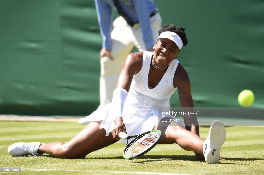 TOPSHOT - US player Venus Williams falls while playing Sweden's Johanna Larsson during their women's singles first round match on the first day of the 2018 Wimbledon Championships at The All England Lawn Tennis Club in Wimbledon, southwest London, on July 2, 2018. (Photo by Oli SCARFF / AFP) / RESTRICTED