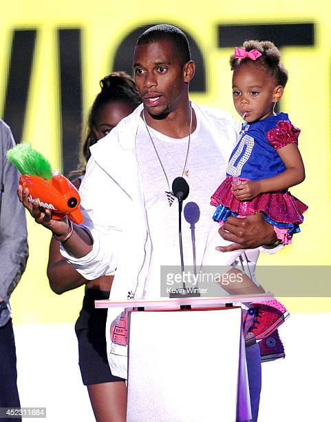 NFL player Victor Cruz with daughter Kennedy Cruz accepts Party Like a Sports Star onstage during Nickelodeon Kids' Choice Sports Awards 2014 at...