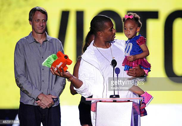 NFL player Victor Cruz with daughter Kennedy Cruz accepts Party Like a Sports Star from skateboarder Tony Hawk onstage during Nickelodeon Kids'...
