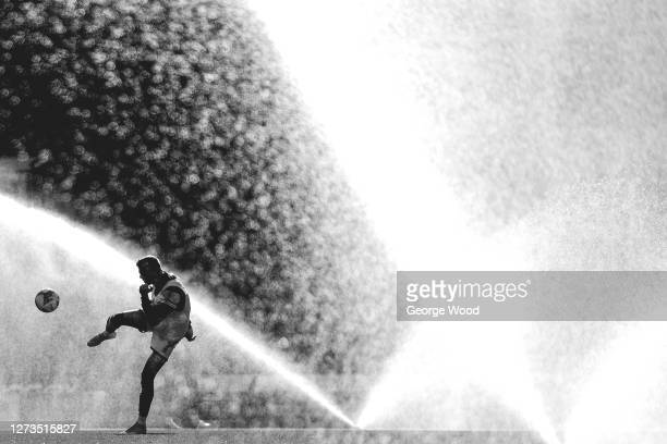 A player warms up at half time as sprinklers water the pitch during the Sky Bet League Two match between Harrogate Town and Walsall at The Keepmoat...