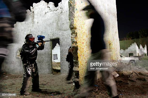 A player who have been shot walks out with his hands in the air as other players continue a paintball game at Hollywood Sports Park in Bellflower...