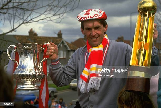 Player/Manager Kenny Dalglish of Liverpool poses with the FA Cup and the Canon League Division One trophy during their homecoming after the FA Cup...