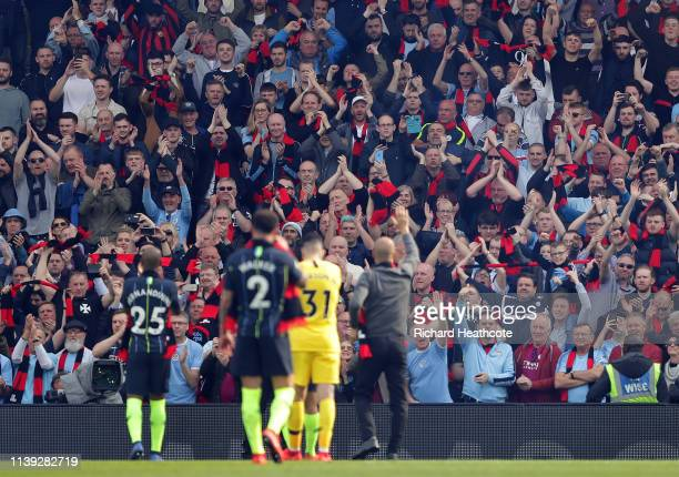 Players acknowledge the fans as they hold up red and black scarves in tribute to Bernard Halford former club secretary following the Premier League...