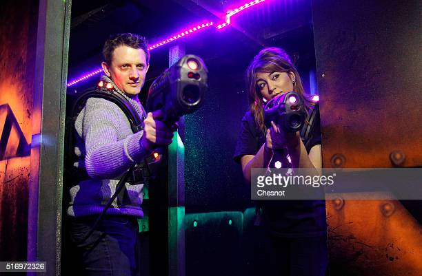 Players aim with laser guns a games centre 'Laser Game Evolution' on March 22 2016 in Grenoble France Laser Game Evolution the French leader of...
