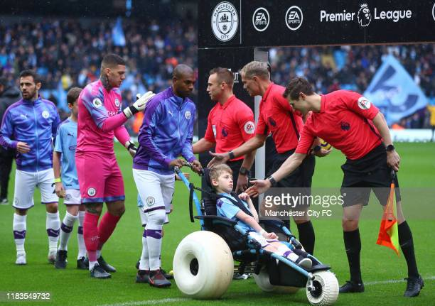 Players and a young fan shake hands prior to the Premier League match between Manchester City and Aston Villa at Etihad Stadium on October 26, 2019...