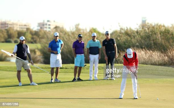 Players and caddies look on as Christofer Blomstrand of Sweden putts for a par to earn his card during the final round of the European Tour...