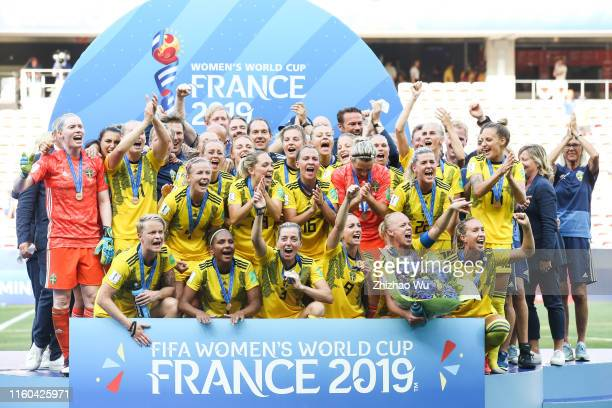Players and coach of Sweden celebrate during the award ceremony after the 2019 FIFA Women's World Cup France 3rd Place Match match between England...