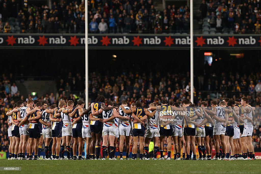 Players and coaches from both teams huddle in the center circle for a moments silence to remember Adelaide Crows coach Phil Walsh during the round 15 AFL match between the West Coast Eagles and the Adelaide Crows at Domain Stadium on July 11, 2015 in Perth, Australia.