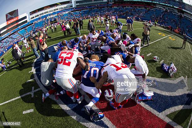 Players and coaches join for a prayer at center field after the game between the Buffalo Bills and the New York Giants on October 4 2015 at Ralph...