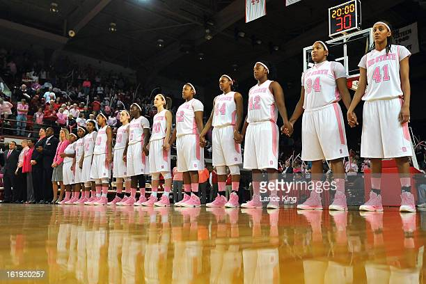 Players and coaches of the North Carolina State Wolfpack stand at attention during the National Anthem prior to a game against the Georgia Tech...