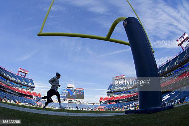 Players and coaches work out under the goal posts at Nissan Stadium before a game between the Denver Broncos and the Tennessee Titans at Nissan...