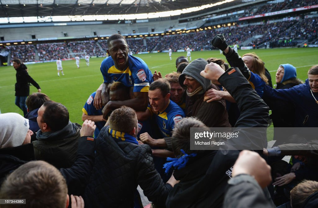Players and fans celebrate as Jack Midson scores their first goal during the FA Cup with Budweiser Second Round match between MK Dons and AFC Wimbledon at StadiumMK on December 2, 2012 in Milton Keynes, England. This match is the first meeting between the two teams following the formation of AFC Wimbledon (the football club formed in 2002 by supporters unhappy with their club's relocation to Milton Keynes) and the MK Dons (which Wimbledon F.C. controversially became).