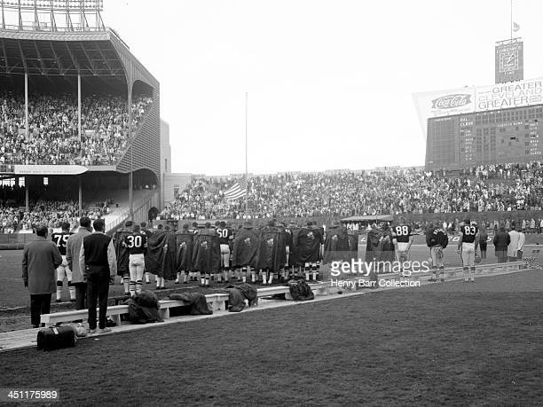 Players and fans pause prior to a game on November 24 1963 between the Dallas Cowboys and the Cleveland Browns at Municipal Stadium in Cleveland Ohio...
